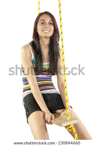 Pretty young brunette happily swings on a swing in casual attire head upward. In studio on white background.