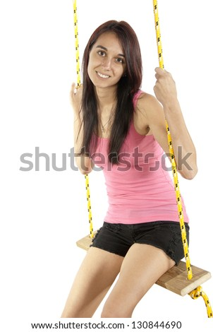 Pretty young brunette happily swings on a swing in casual attire. In studio on white background.