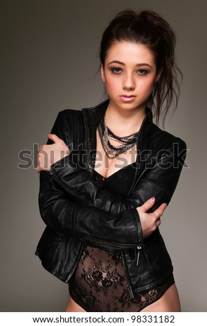 Pretty young brunette in a black leotard and leather jacket