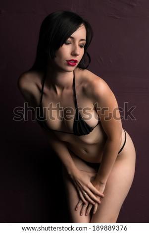 Pretty young brunette in a skimpy black bikini #189889376