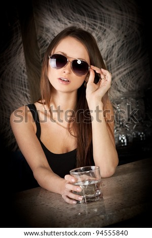 Pretty young brunette lady with a glass of vodka