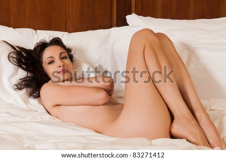 Pretty young brunette lying nude in bed
