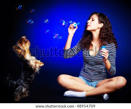 pretty young brunette woman and her dog with soap bubbles against blue background