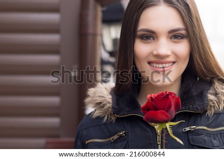 Pretty young brunette woman and red rose. Portrait of beautiful woman with red rose