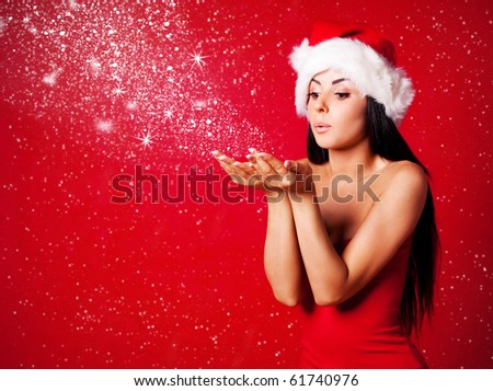 pretty young brunette woman dressed as Santa blowing on the snow on her hands