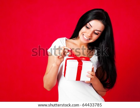 pretty young brunette woman dressed in red dress opening a present