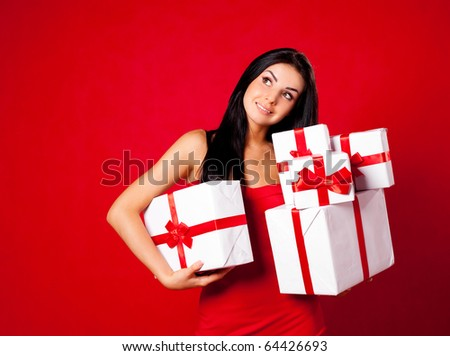 pretty young brunette woman dressed in red dress with many presents