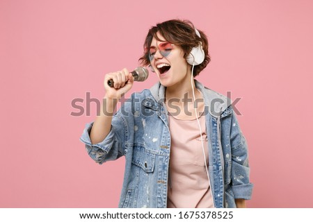 Pretty young brunette woman in casual denim jacket, eyeglasses isolated on pastel pink background. People lifestyle concept. Mock up copy space. Listen music with headphones sing song in microphone Photo stock ©