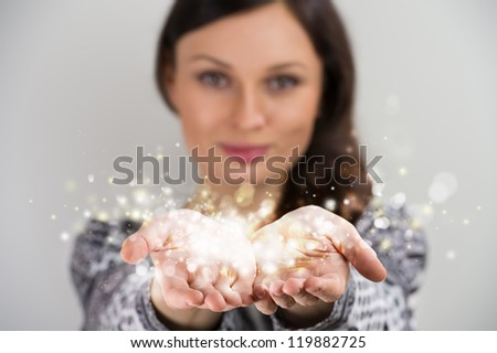 Pretty young brunette woman smiling against gray background with magic sparkle in her hands cupped together