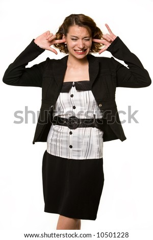 Pretty young brunette woman wearing business attire sticking her fingers in ears with an annoyed expression to show not listening standing on white