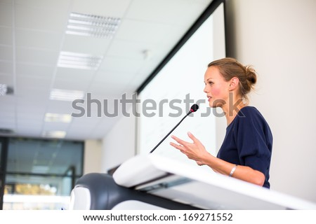 Pretty young business woman giving a presentation in a conference/meeting setting (shallow DOF; color toned image) - stock photo