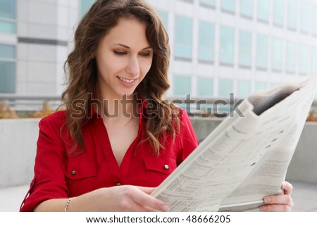Pretty young business woman reading newspaper at office building