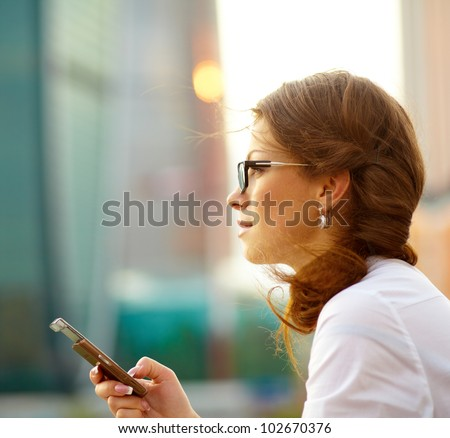 Pretty young business woman using mobile phone outdoor stock photo