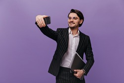 Pretty young businessman with brunette hair, glasses, white shirt and striped suit, smiling, making selfie and holding folders in one hand. Man posing isolated over violet background