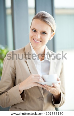 pretty young businesswoman having coffee break at work
