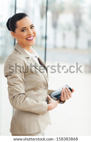 pretty young businesswoman holding tablet computer at workplace