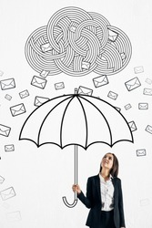 Pretty young businesswoman protecting himself from email cloud rain with drawn umbrella. Communication overload concept