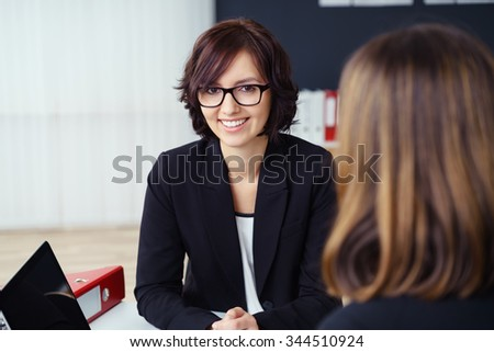 Pretty Young Businesswoman Smiling at the Camera While Talking with her Co-worker During a One-on-One Meeting inside the Office. #344510924