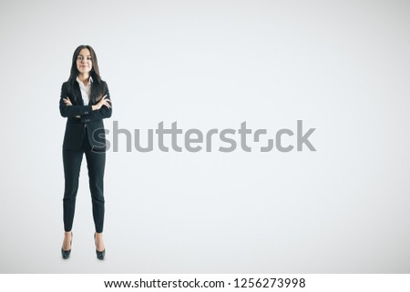 Pretty young businesswoman with folded arms standing on white background with copy space. Confidence concept