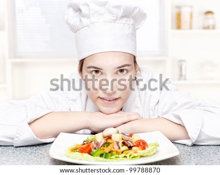 pretty young chef and hers plate of a delicious salad in kitchen