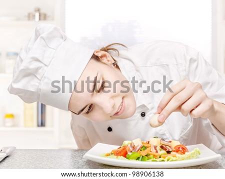 pretty young chef decorating delicious salad