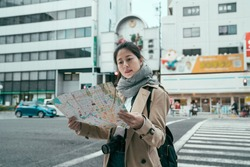 pretty young chinese woman using paper map on city street outdoors. Beautiful lady tourist walking on zebra cross in dotonbori to shinsaibashi. girl backpacker self guided trip in spring osaka japan.