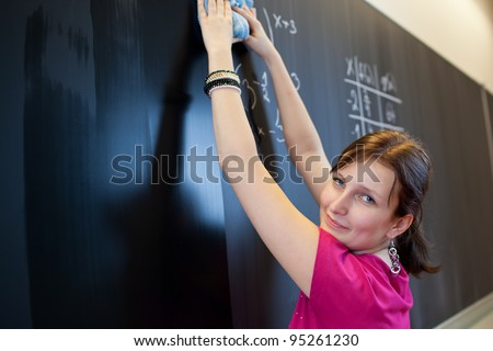 pretty young college student erasing the chalkboard/blackboard during a math class (color toned image; shallow DOF) - stock photo