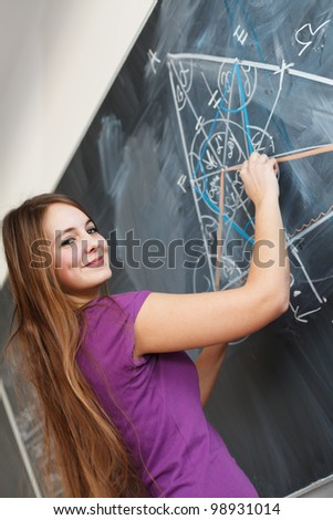 pretty young college student writing on the chalkboard/blackboa rd during a math class (color toned image; shallow DOF) - stock photo