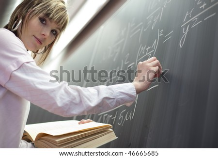 pretty young college student writing on the chalkboard/blackboard during a math class
