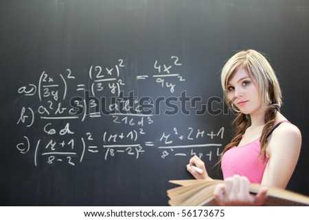 pretty young college student writing on the chalkboard/blackboard during a math class (color toned image)