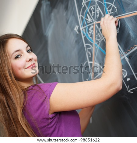 pretty young college student writing on the chalkboard/blackboard during a math class (color toned image; shallow DOF)
