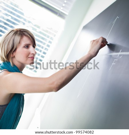 pretty young college student/young teacher writing on the chalkboard/blackboard during a math class (color toned image; shallow DOF)