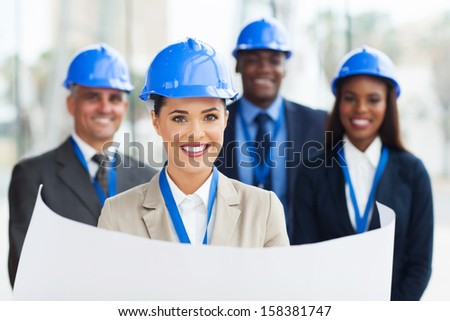 pretty young construction manager holding blue print in front of colleagues