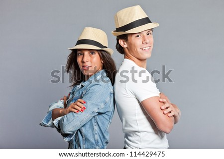 Pretty young couple casual dressed wearing a straw hat. Brother and sister. Good looking. Brown hair and eyes. Studio portrait isolated on grey background.