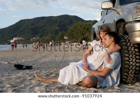pretty young couple sit near wheel on the sand beach of phuket