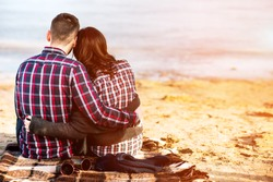 Pretty young couple sitting on the beach
