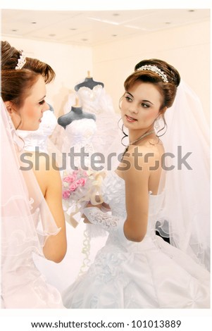 pretty young excited woman is choosing a wedding dress in the shop