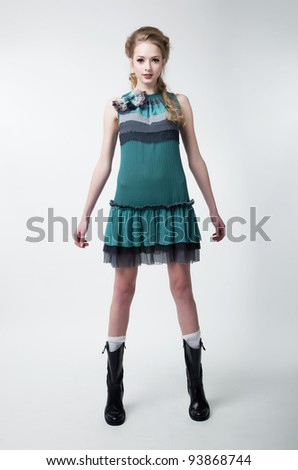 Pretty young fashion model female in contemporary dress posing in studio. Series of photos