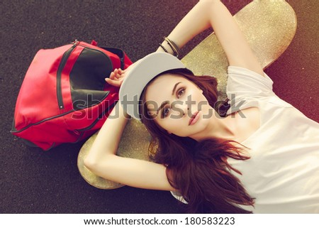 Pretty young fashion woman outdoor summer colorful closeup portrait Brunette girl posing on the ground with backpack and skate