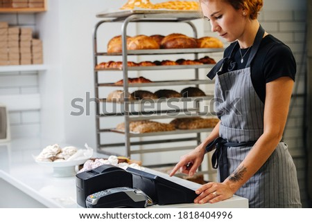 Pretty young female baker standing behing cash register calculating overal cost of the order. Side view. Cropped, half head.