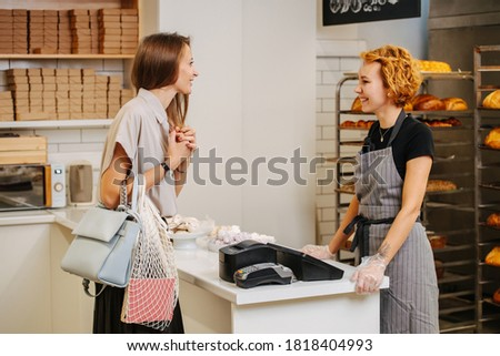 Pretty young female baker standing behing cash register talking to client, taking her order, charmingly smiling. Side view.