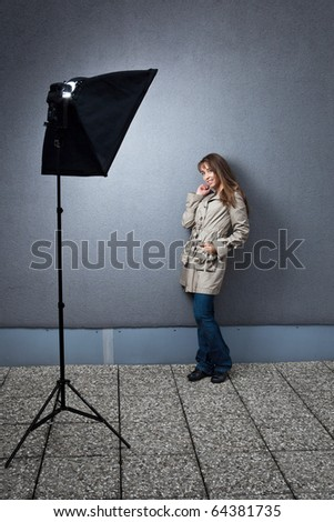 Stock Photo Pretty young female caucasian model being photographed on location - lit by a strobe in a softbox (color toned image)
