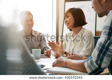 Pretty young female entrepreneur talking to her employees at meeting