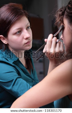 Pretty young female model having her makeup applied before her photoshoot