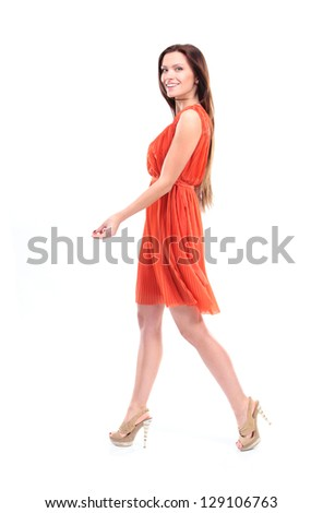 Pretty young female model in dress walking on white background and smiling - Copysapce