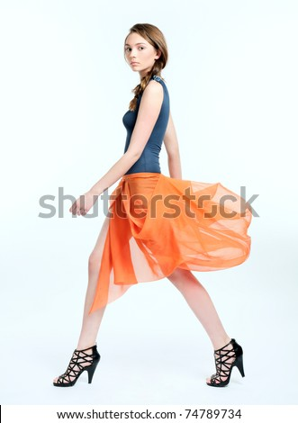 Pretty young female model in orange dress walking on white background