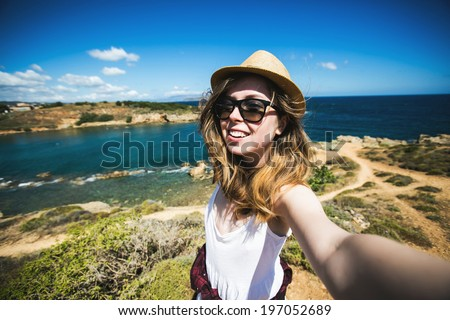 Pretty young female tourist takes travel selfie at the beach while summer vacation on Crete island in Greece