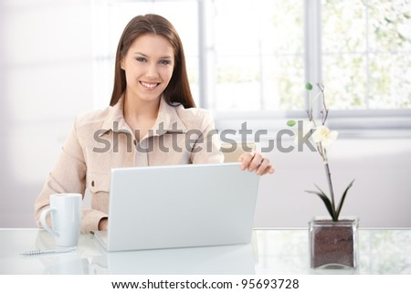 Pretty young female using laptop at home, sitting at desk, smiling.?