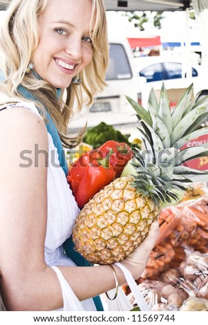pretty young girl at the market buying fruit and vegtables