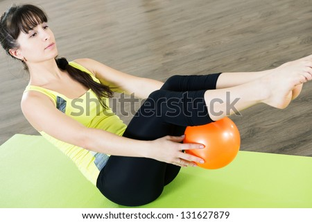 Pretty young girl fitness workout with small ball
